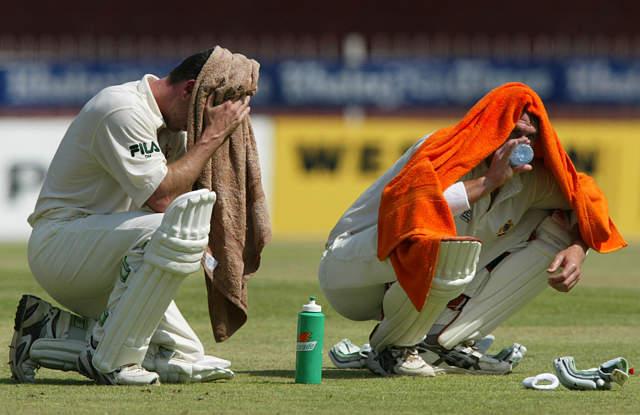 آسٹریلیا 2002ء کے یہ مناظر نہیں بھول سکتا، ڈیمین مارٹن (بائیں) اور میتھیو ہیڈن (دائیں) شارجہ میں پاکستان کے خلاف ٹیسٹ کے دوران گرمی سے بچنے کی ناکام کوششیں کرتے ہوئے (تصویر: Reuters)