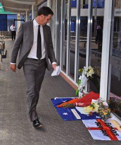 کرکٹ آسٹریلیا کے سربراہ جیمز سدرلینڈ سڈنی کرکٹ گراؤنڈ کے باہر فلپ ہیوز کی یاد میں رکھے گئے گلدستوں کے پاس سے گزر رہے ہیں (تصویر: Getty Images)