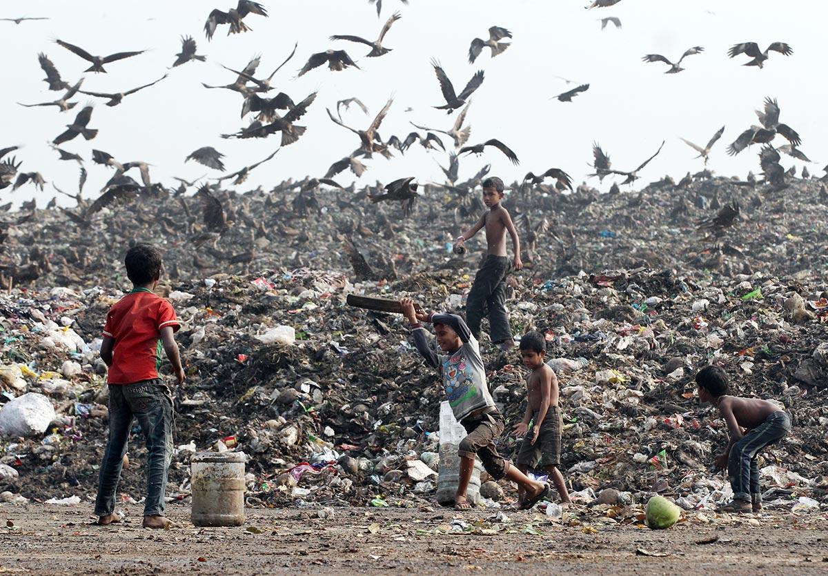 بنگلہ دیش کے شہر ڈھاکہ میں بچے کچرے میں ڈھیر کے ساتھ کرکٹ کھیلتے ہوئے (تصویر: Abu Taher Khokon)