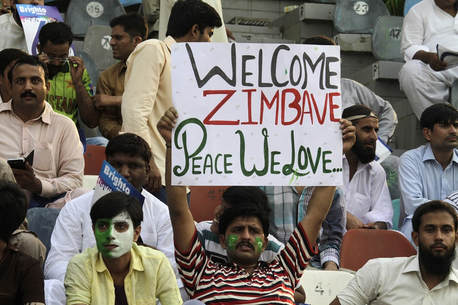 Pakistan's cricket fans hold up a poster to welcome Zimbabwe cricket team at the Gaddafi stadium in Lahore, Pakistan, Friday, May 22, 2015. The game marks a return of international cricket to Pakistan for the first time since gunmen attacked buses carrying the Sri Lankan cricket team and match officials in this eastern city six years ago.  (AP Photo/K.M. Chaudary)