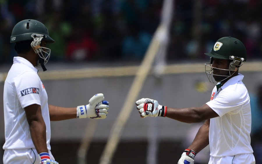 Bangladesh cricketer Tamim Iqbal (L) celebrates with teammate Imrul Kayes (R) after hitting a boundary during the fourth day of the first cricket Test match between Bangladesh and Pakistan at The Sheikh Abu Naser Stadium in Khulna on May 1, 2015. AFP PHOTO/Munir uz ZAMAN        (Photo credit should read MUNIR UZ ZAMAN/AFP/Getty Images)