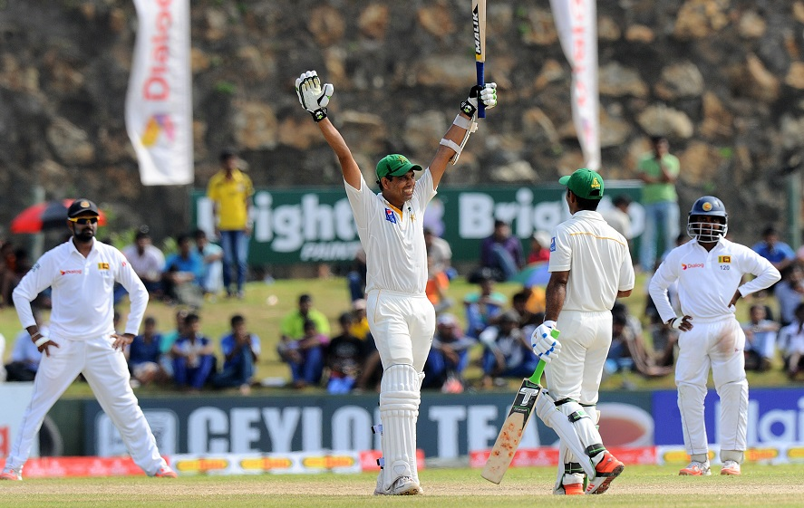 Pakistan cricketer Zulfiqar Babar (2L) raises his bat to the crowd after scoring a half-century (50 runs) as teammate Asad Shafiq (2R) looks on during the fourth day of the opening Test match between Sri Lanka and Pakistan at the Galle International Cricket Stadium in Galle on June 20, 2015. AFP PHOTO/ Ishara S. KODIKARA        (Photo credit should read Ishara S.KODIKARA/AFP/Getty Images)